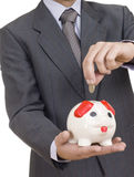 A businessman putting a coin into a piggy bank Royalty Free Stock Photos