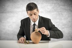 Businessman putting coin into the piggy bank Stock Image