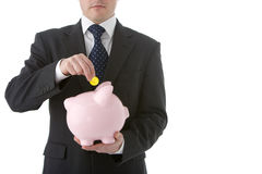 Businessman Putting Coin Into Piggy Bank Stock Photo