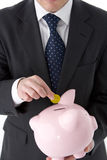Businessman Putting Coin Into Piggy Bank Stock Photos