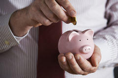 Businessman Putting Coin Into Piggy Bank Royalty Free Stock Images