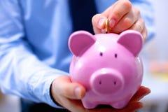 Businessman putting coin into small piggy bank Stock Photos
