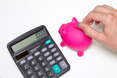 Businessman putting coin into small piggy bank. Calculator showi Royalty Free Stock Photos
