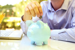 Businessman putting coin to the pig box. Laptop behind.  Stock Photography