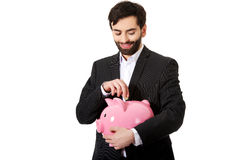 Businessman putting a coin to piggy bank. Royalty Free Stock Image