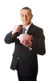Businessman putting a coin to piggybank Stock Photography