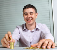 Businessman putting the coins in columns Royalty Free Stock Images