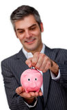 Businessman putting coins in a piggy bank Royalty Free Stock Images