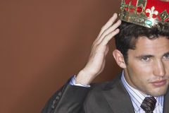 Businessman Putting On Crown Stock Images