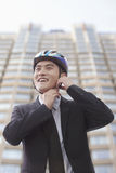 Businessman putting on cycling helmet Stock Photo