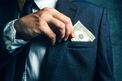 Businessman putting dollar banknotes money in his suit pocket Royalty Free Stock Images