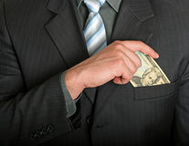 Businessman putting a dollar bill in his pocket. Businessman putting a dollar bill in his suit pocket Royalty Free Stock Images