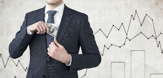 Businessman putting dollars in pocket, graphs Stock Photography