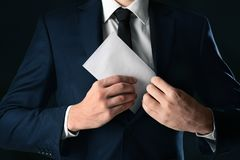 Businessman putting envelope with bribe in pocket. On black background Royalty Free Stock Photos