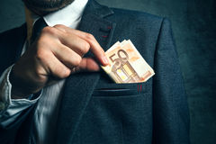 Businessman putting euro banknotes money in his suit pocket Stock Image