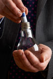 Businessman Putting Euro Note Into Light Bulb Stock Photography