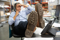 Businessman Putting Feet Up On Desk In Warehouse. On Phone Stock Photography