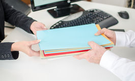 Businessman putting files in the hands of his secretary Royalty Free Stock Photos