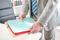 Businessman putting files on his desk Stock Photos