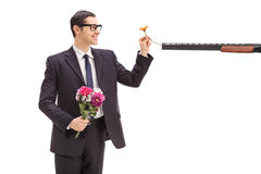 Businessman putting a flower in a rifle Stock Photos