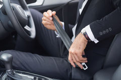 Businessman putting on his seat belt. In his car Stock Photography