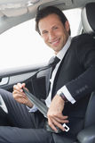 Businessman putting on his seat belt Stock Images