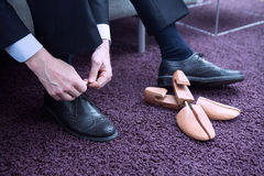 Businessman putting his shoes on. Businessman sitting on couch and tying his shoelaces Stock Images