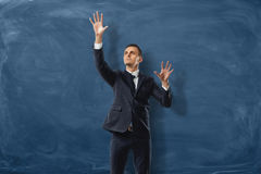 Businessman is putting imaginary buttond on the blue blackboard background Stock Photography