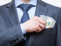 Businessman putting money in the breast pocket Royalty Free Stock Image