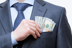 Businessman putting money in the breast pocket Royalty Free Stock Photo