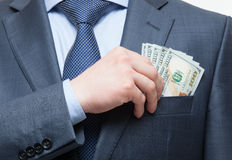 Businessman putting money in the breast pocket Stock Images