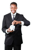Businessman putting money in his piggy bank Stock Images