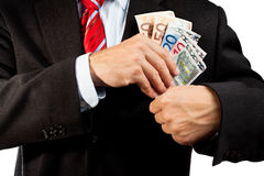 Businessman putting money in his pocket. Stock Images