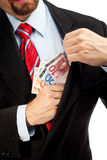 Businessman putting money in his pocket. Stock Photography