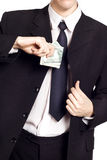 Businessman is putting money in his pocket Stock Photography