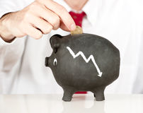 Businessman putting money on a piggy bank Royalty Free Stock Photo