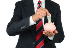 Businessman Putting Money in Piggy Bank Stock Images