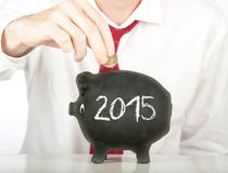 Businessman putting money on a piggy bank Stock Photos