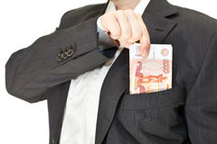 Businessman putting money in the pocket Royalty Free Stock Photos