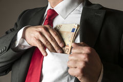 Businessman putting money in pocket. Businessman putting money in his shirt pocket Royalty Free Stock Photography