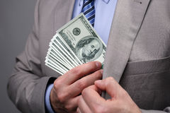 Businessman putting money in pocket. Man putting money in suit jacket pocket concept for corruption, bribing, paying or business wealth Stock Photo