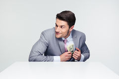 Businessman putting money in pocket Stock Photos