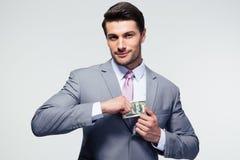Businessman putting money in pocket Stock Image