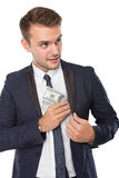 Businessman putting money into pocket Royalty Free Stock Images