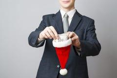 Businessman putting money in a Santa hat Stock Photos