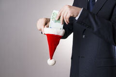 Businessman putting money in a Santa hat Stock Photos