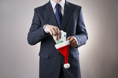 Businessman putting money in a Santa hat Stock Photography