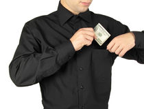 Businessman putting money in shirts' pocket Royalty Free Stock Image