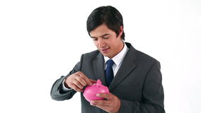 Businessman putting notes in a piggy bank Stock Image