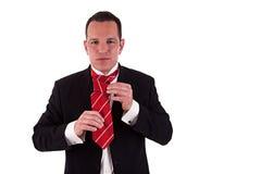 Businessman putting on tie Stock Image